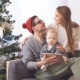 Free Download Happy young family from mom, dad and  little boy on eve of Christmas Nulled