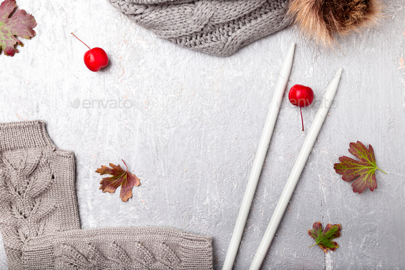 Grey scarf, hat gloves near knitting needles on grey background. Top view. Copy space. flat lay - Stock Photo - Images
