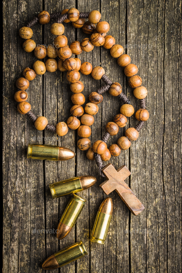 Rosary beads and pistol bullets. - Stock Photo - Images