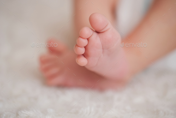 mother holds little foot of newborn baby - Stock Photo - Images