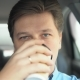 A Man Is Drinking Coffee in a Car - VideoHive Item for Sale