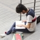 Portrait of a Happy Male Asian Student Sitting on Stairs and Reading Book - VideoHive Item for Sale