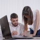 Man Is Sitting on a Chair in Office and Young Woman Is Standing Near, Both Are Looking on a Paper on