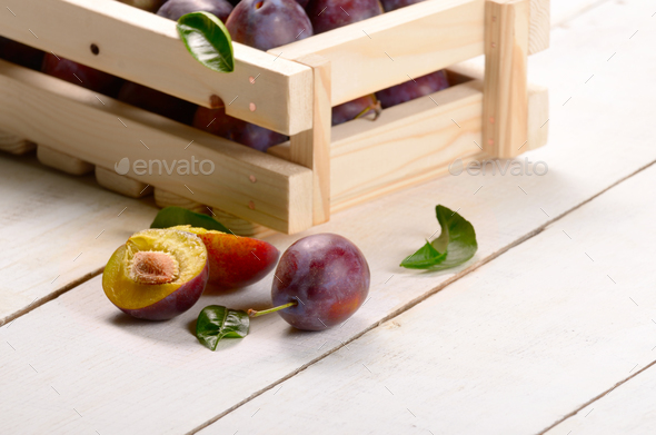 Wooden crate with plums closeup - Stock Photo - Images
