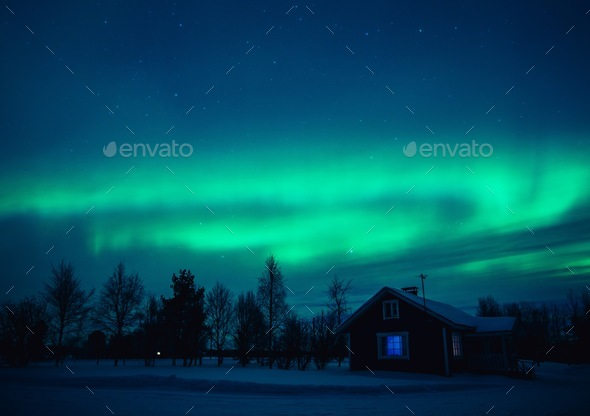 Northern lights (Aurora Borealis) over  cottage in Lapland village. Finland - Stock Photo - Images