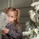 The Girl Plays Near a New Year Tree with a White Feather. - VideoHive Item for Sale