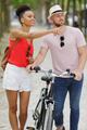 man on a bike woman standing next to him