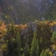 Aerial Shot of a Small Waterfall Flowing in Canyon with Autumn Mountain Forests - VideoHive Item for Sale