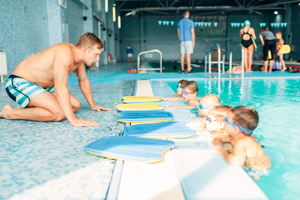 Instructor talking to children in the pool - Stock Photo - Images