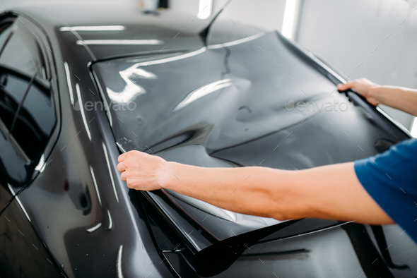 Male specialist with car tinting film in hands - Stock Photo - Images