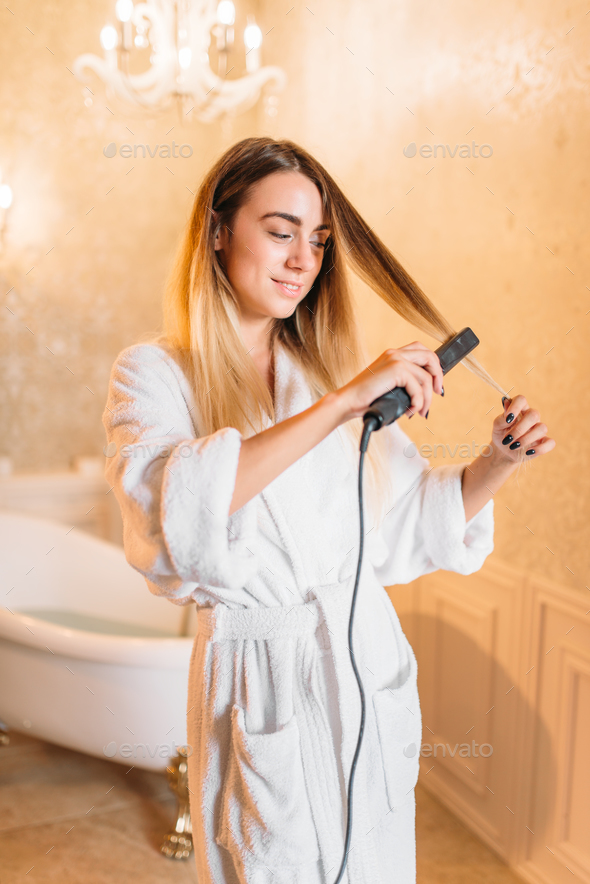 Woman with curling iron, bathroom on background - Stock Photo - Images