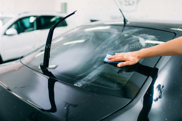 Specialist prepairs the window, car tinting film - Stock Photo - Images