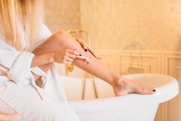 Female person in white bathrobe shaves legs - Stock Photo - Images