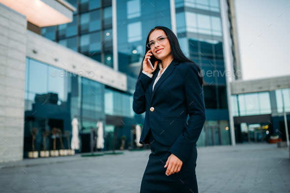 Businesswoman in suit talks by phone outdoor - Stock Photo - Images