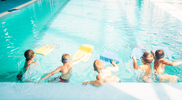 Boys starts simming in pool with plank - Stock Photo - Images