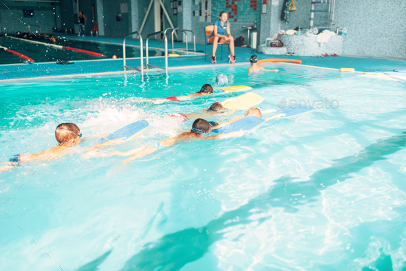 Boys swimming with plank in a pool race - Stock Photo - Images