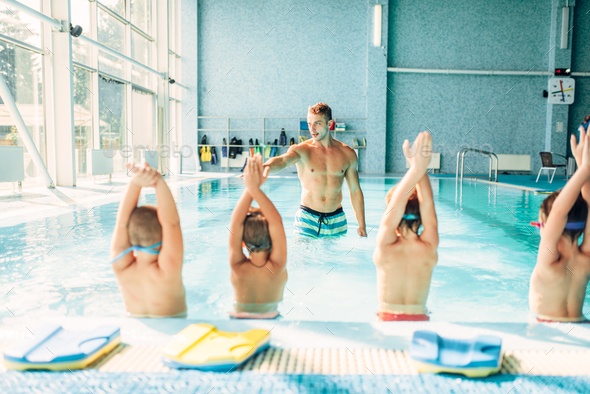 Kids doing exercise in swimming pool - Stock Photo - Images