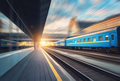 Beautiful train with blue wagons in motion at the railway statio - PhotoDune Item for Sale