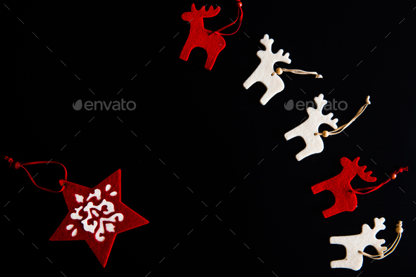 Red and white felt rein deers and snowflake isolated on black. Christmas background  - Stock Photo - Images