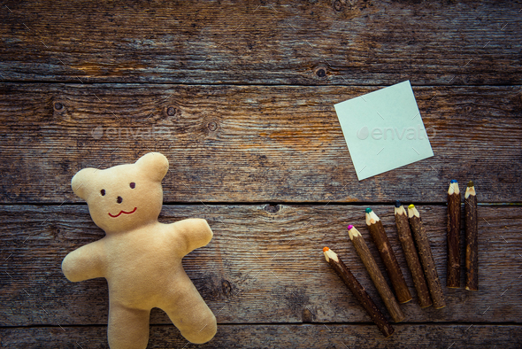 Teddy bear, sticky note and colored pencils on wooden background - Stock Photo - Images