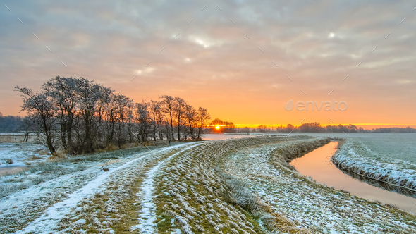 Dike near Meandering River in Frozen grassland landscape - Stock Photo - Images