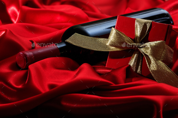 Valentines day. Red wine bottle and a gift on red satin - Stock Photo - Images