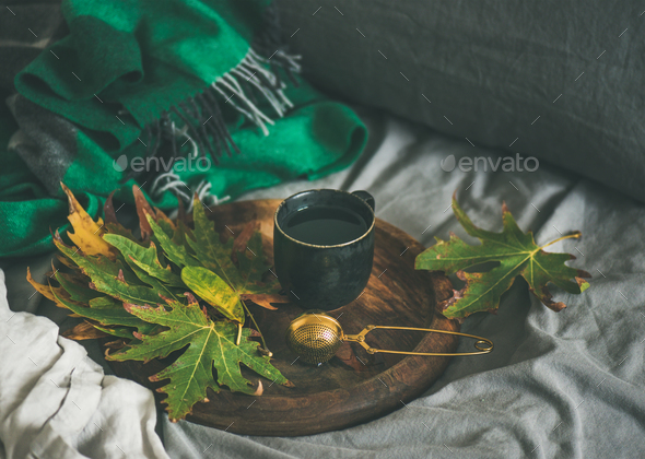 Black mug of tea with sieve and leaves on tray - Stock Photo - Images
