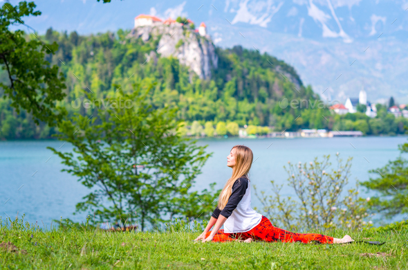 Woman doing yoga by the lake - Stock Photo - Images