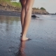Young Woman Walking Along the Water's Edge. Woman Going Along the Shore on Black Sand. The Camera Is - VideoHive Item for Sale