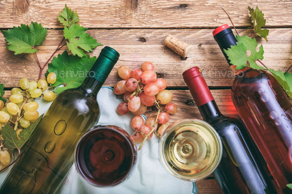 Red and white wine glasses and bottles on wooden background. Fresh grapes and grape leaves - Stock Photo - Images