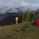 Aerial Footage of a Man Standing Near a Tent in Front of Mountain Valley. - VideoHive Item for Sale