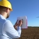 Engineer Looks at the Windmill Drawings on the Background of a Windmill. - VideoHive Item for Sale