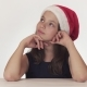 Beautiful Teen Girl in Santa Claus Hat Sitting and Dreaming of a Gift, Expresses Happiness and - VideoHive Item for Sale
