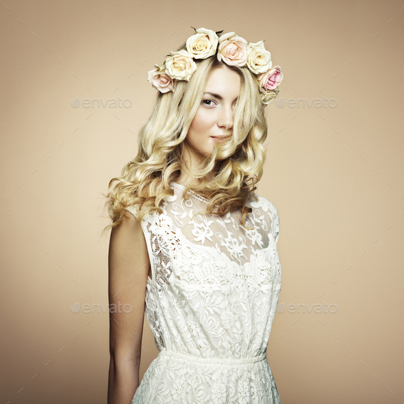 Portrait of a beautiful blonde woman with flowers in her hair - Stock Photo - Images