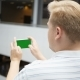 Young Teenager Playing Game on Smartphone in Cafe. Young Happy Man Playing Games on Smartphone - VideoHive Item for Sale