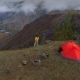 Aerial Footage of a Man Standing Near a Tent in Front of Mountain Valley, - VideoHive Item for Sale