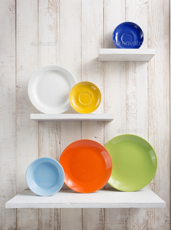 plate at kitchen shelf on wooden background - Stock Photo - Images