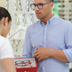 optician showing glasses to woman at optics store - PhotoDune Item for Sale