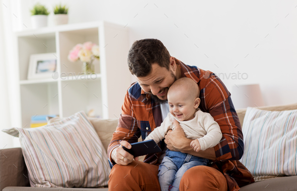 father and baby boy with smartphone at home - Stock Photo - Images