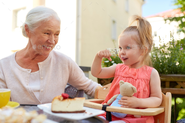 little girl with grandmother eating cafe - Stock Photo - Images