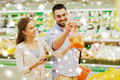 happy couple buying oranges at grocery store