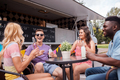 friends with drinks sitting at table at food truck - PhotoDune Item for Sale