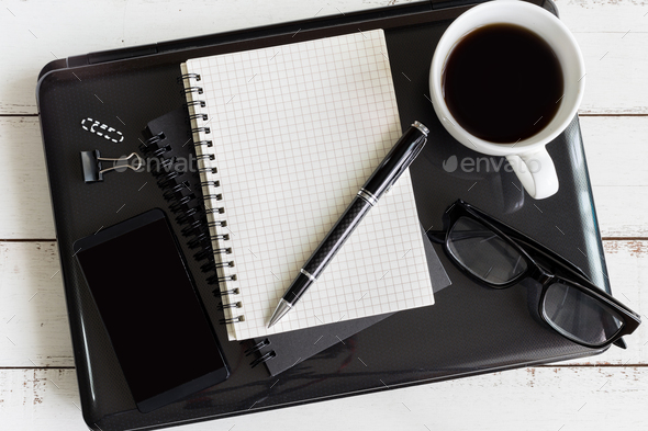 Notebook with laptop and cup of coffee on wooden desk - Stock Photo - Images