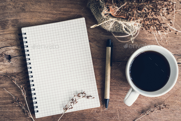 Notebook with cup of coffee on old wooden table - Stock Photo - Images