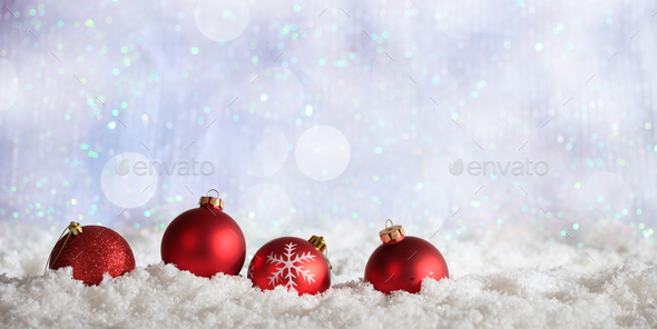 Red Christmas balls row on Christmas snowy bokeh background - Stock Photo - Images