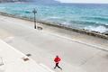 Girl running on city street at seaside