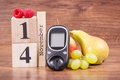 Date 14 November as symbol of world diabetes day, glucometer for measuring sugar level and fruits