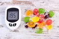 Glucometer with bad result of measurement sugar level and colorful candies