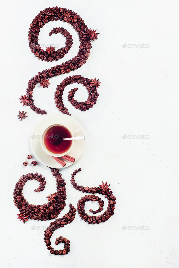 Coffee grains lying in the shape of a swirl with the cup, cinnamon, anise stars and donuts - Stock Photo - Images