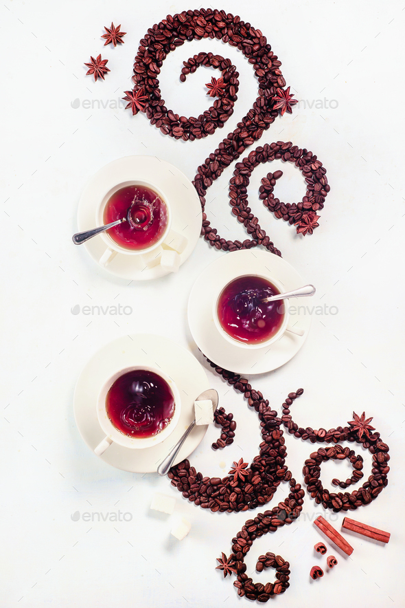 Coffee grains lying in the shape of a swirl with the cup, cinnamon, anise stars - Stock Photo - Images